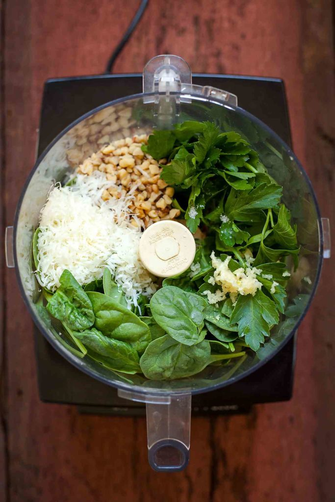 the ingredients for spinach pesto in a food processor before being processed