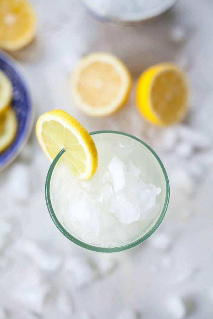 overhead photo of a glass of lemonade with ice and lemons