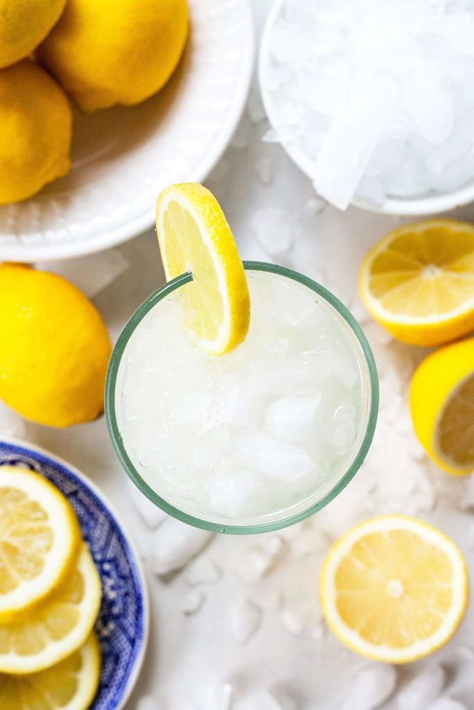 overhead photo of single serving lemonade by the glass with lemons and ice