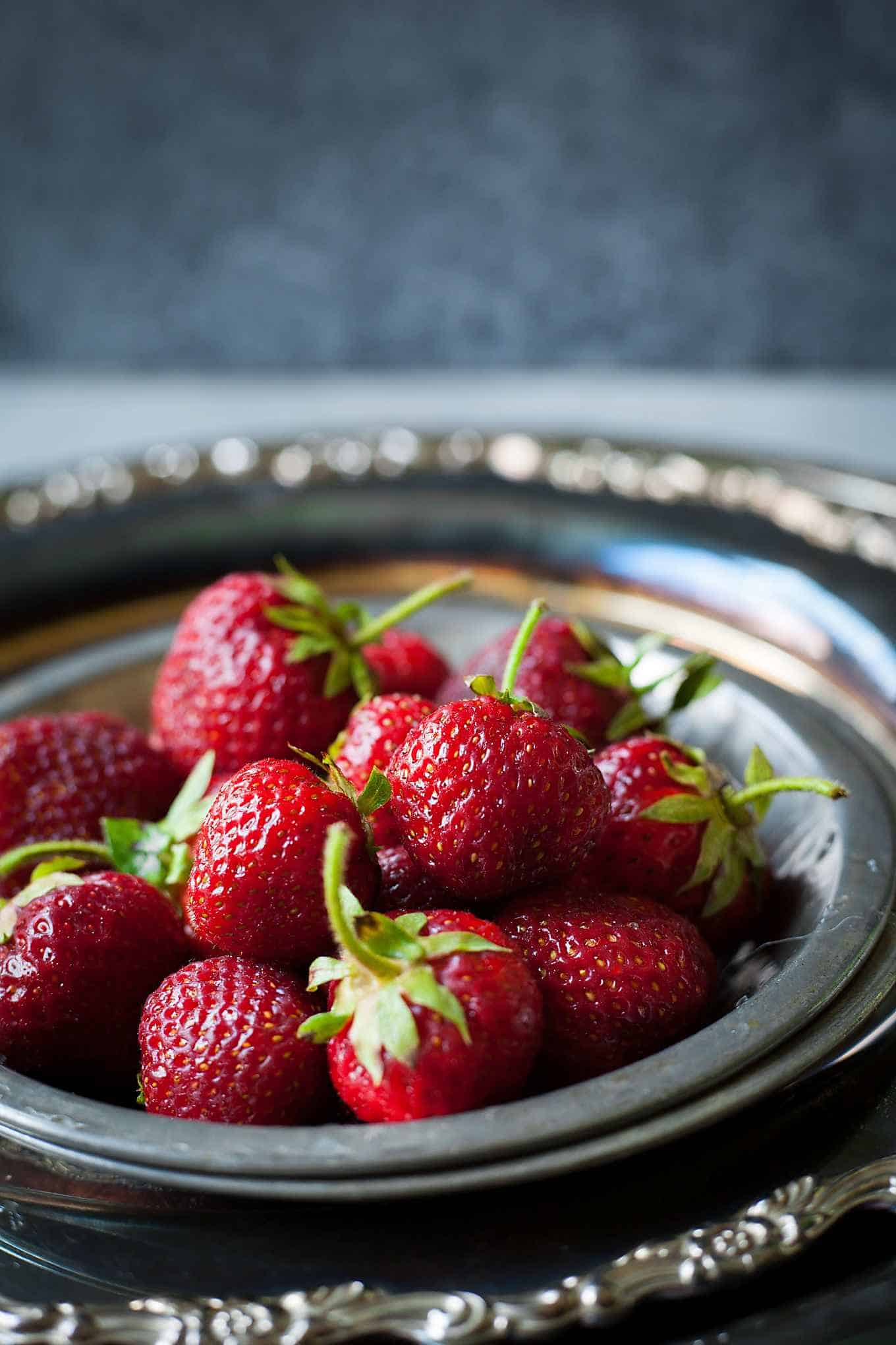 a pile of fresh strawberries on a platter