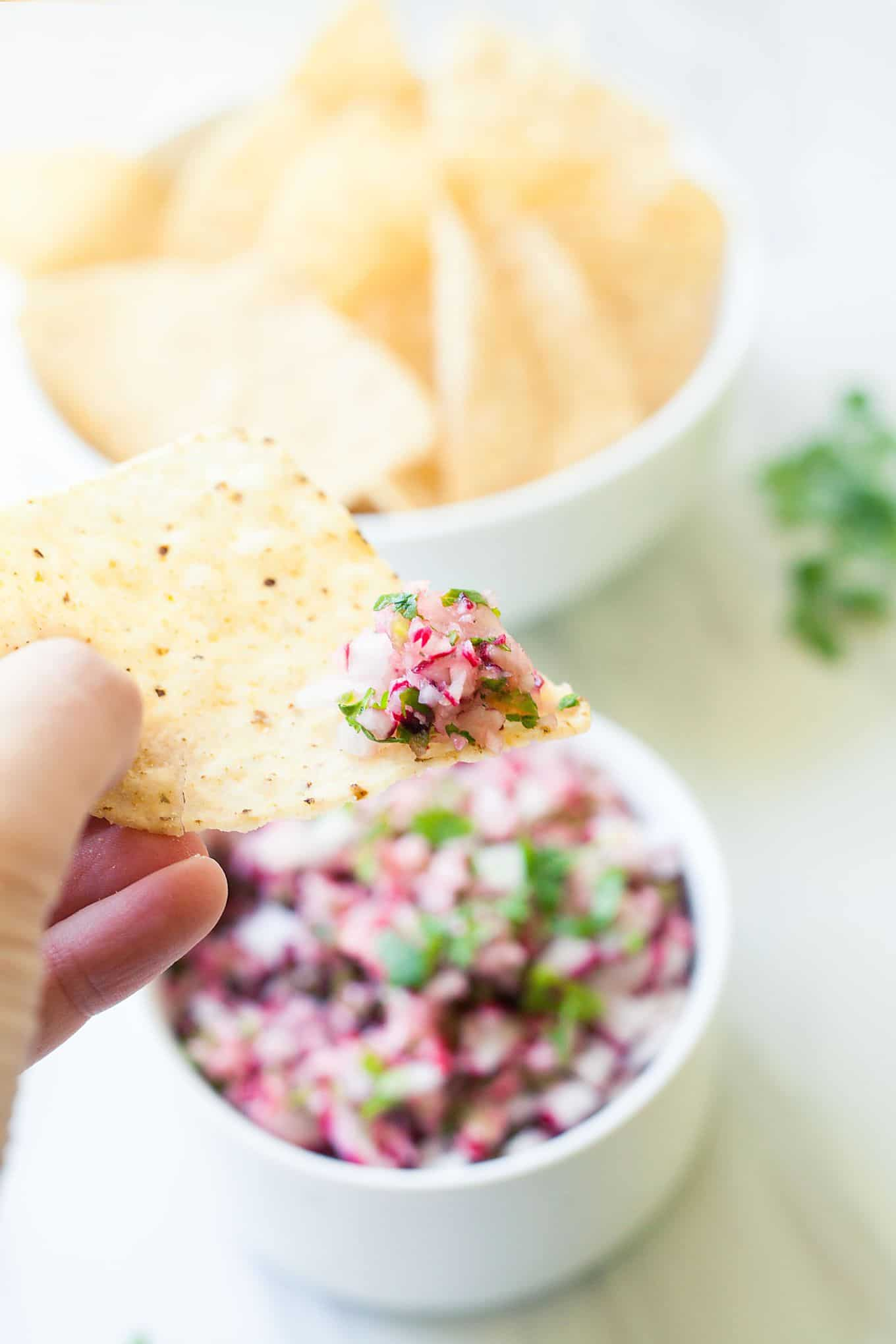 a hand grabbing some radish salsa on a tortilla chip