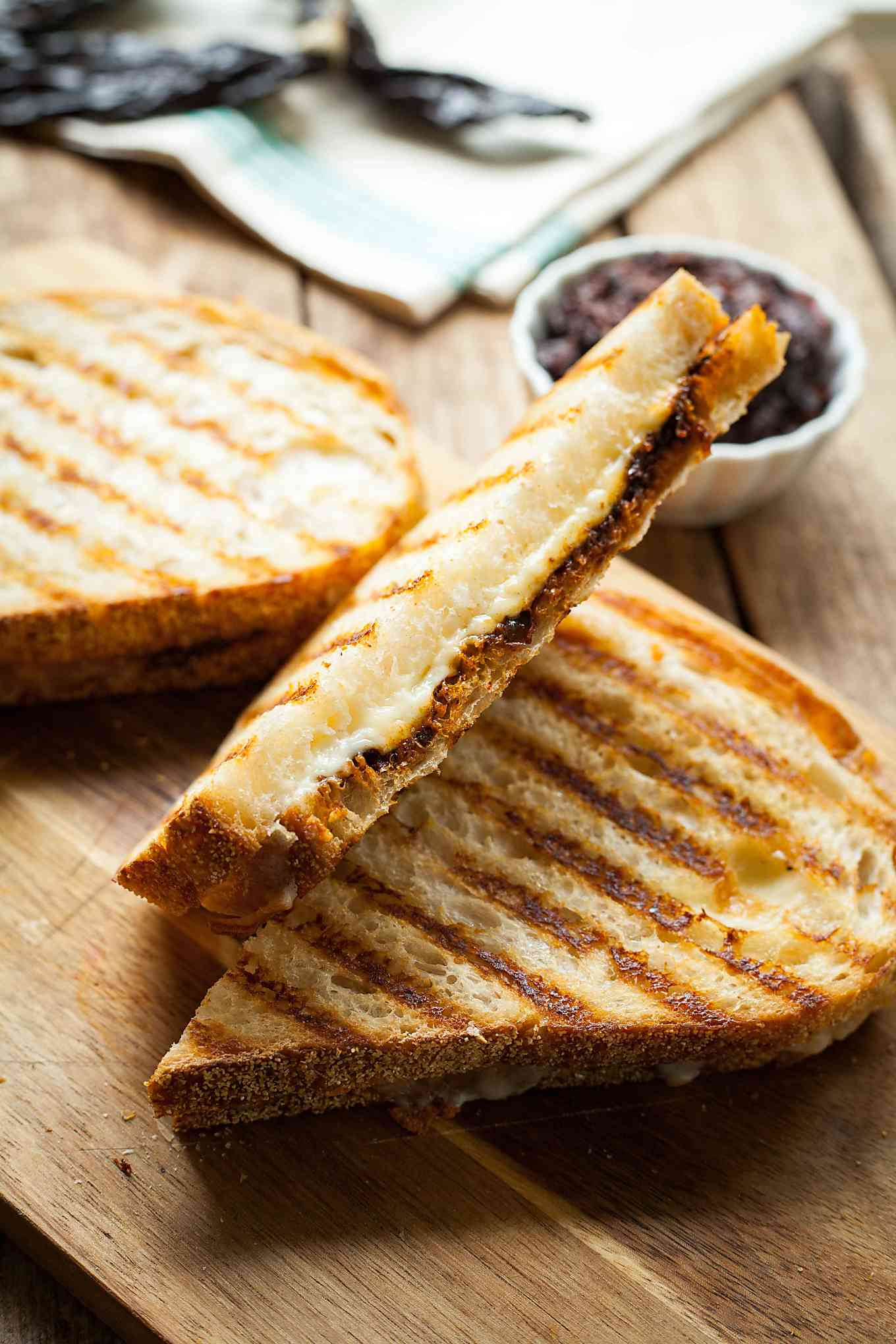 harisssa grilled cheese sandwiches on a wood cutting board