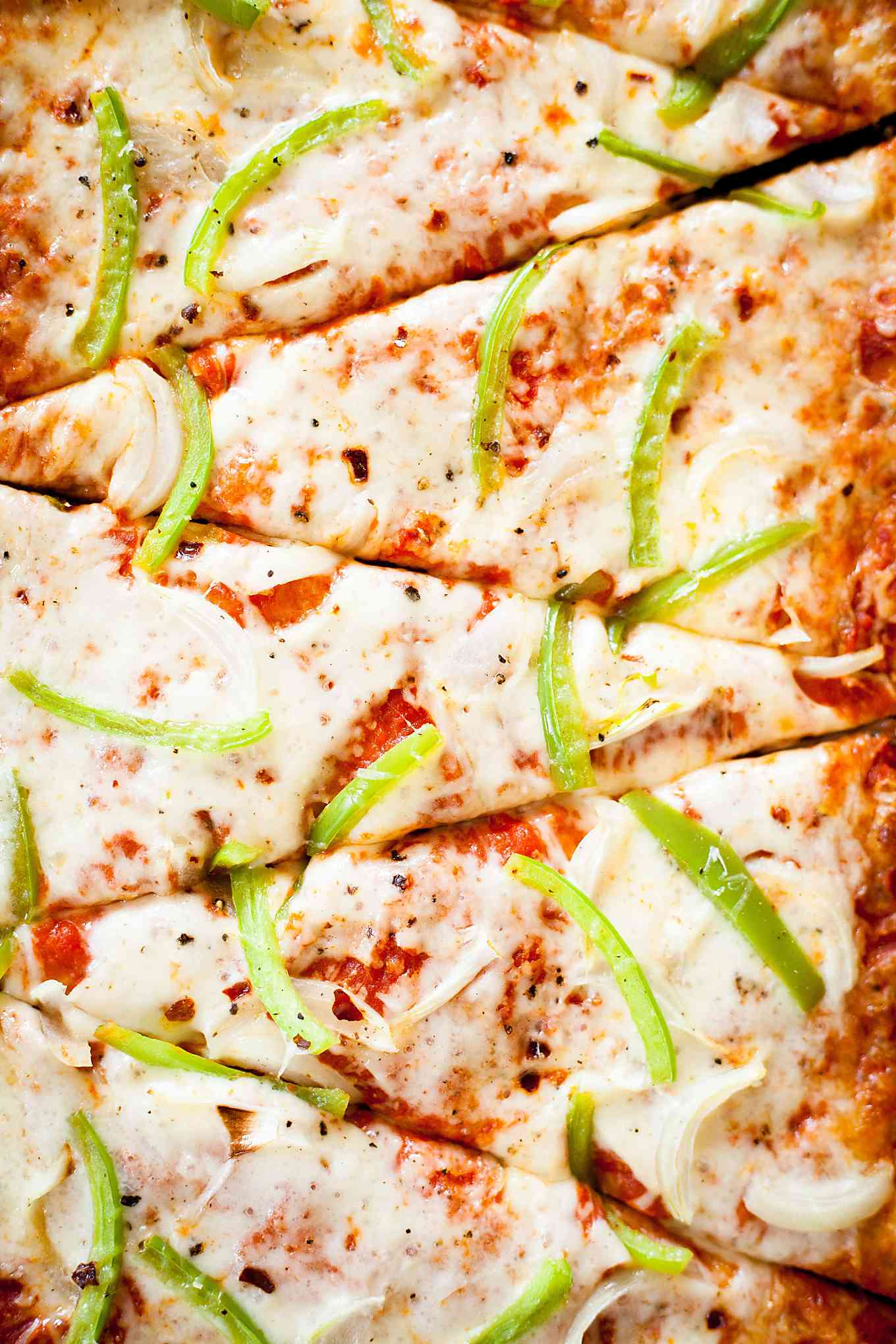 close up of a sliced onion and green pepper pizza