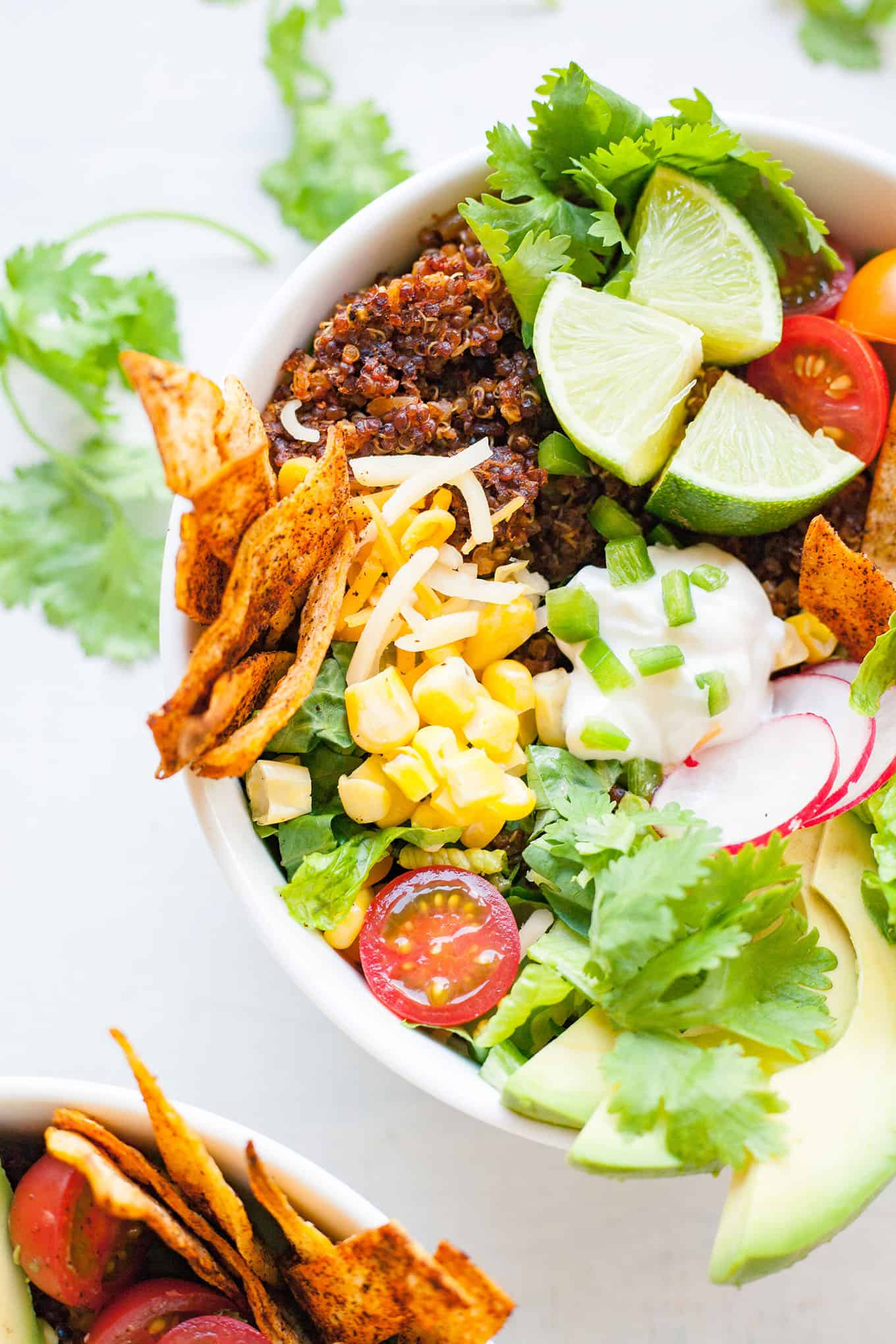 close up photo of vegetables, quinoa taco meat, sour cream, cheese, and tortilla strips in a white bowl