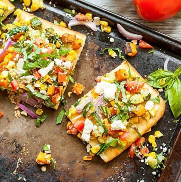 roasted vegetable flatbread on a baking sheet with basil and hummus