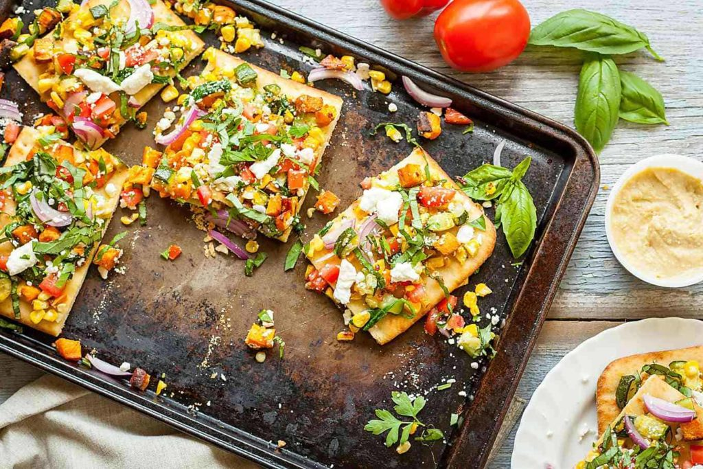 Rainbow Feta Flatbread - Roasted veggies, fresh veggies, and all the herbs! This is the best vegetarian summer meal, especially when you add a side of hummus for protein! Full recipe at theliveinkitchen.com