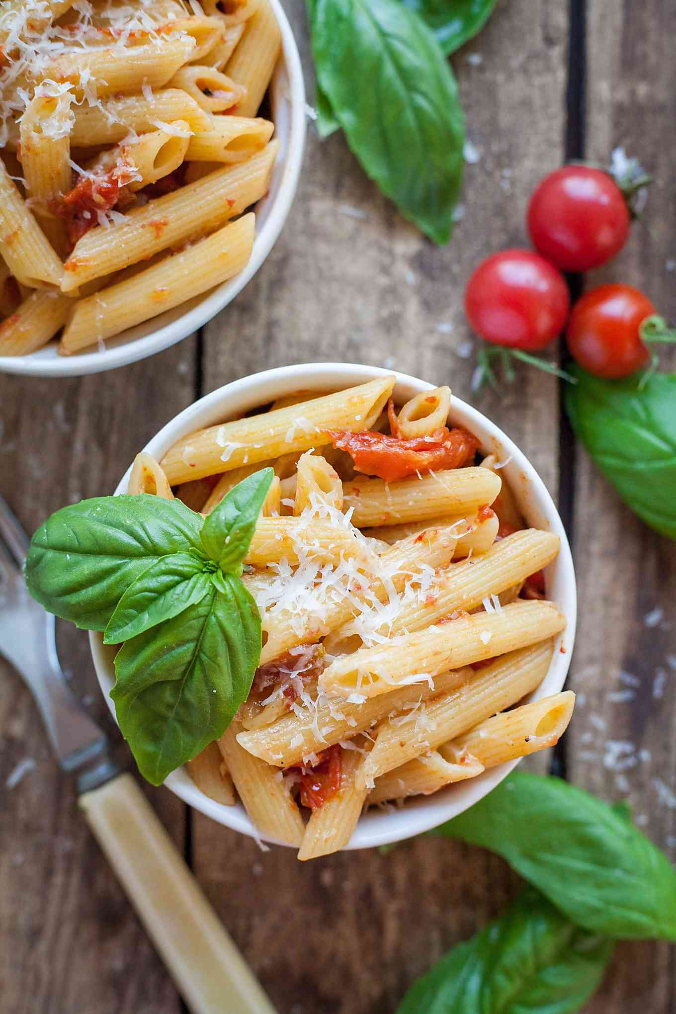 two small bowls of penne pasta with roasted tomato and garlic sauce and basil