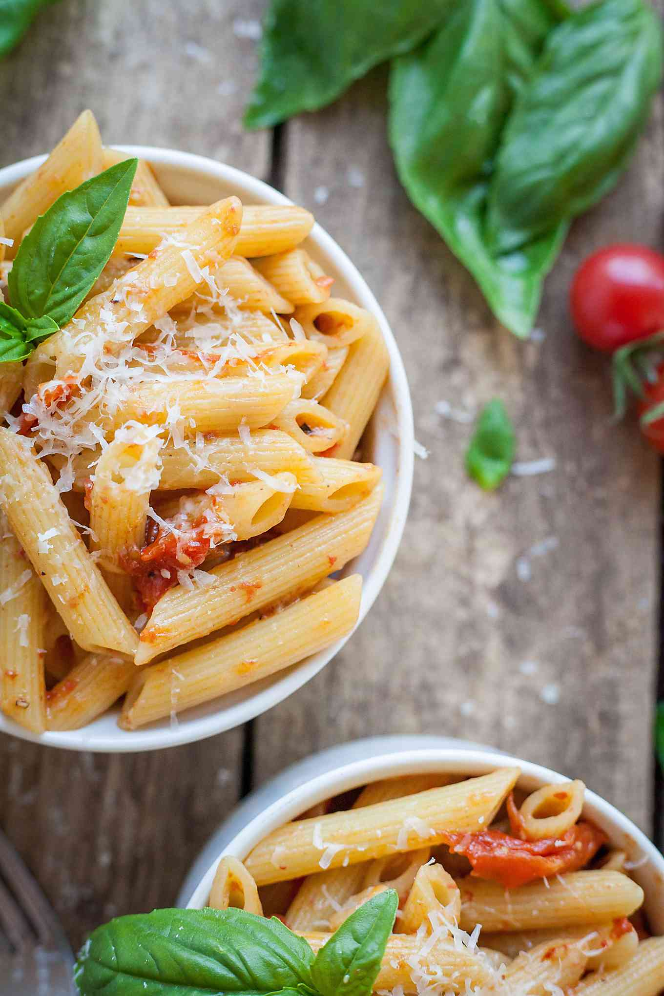 two small bowls of pasta with tomatoes and basil