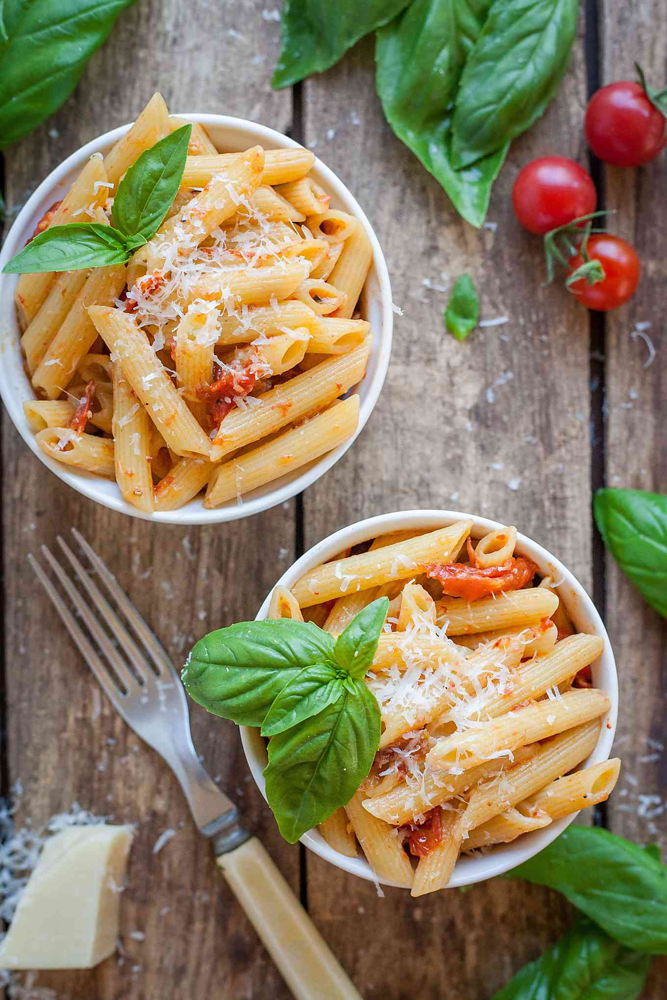 two bowls of penne with roasted tomato and garlic sauce on a wood board with a fork and basil
