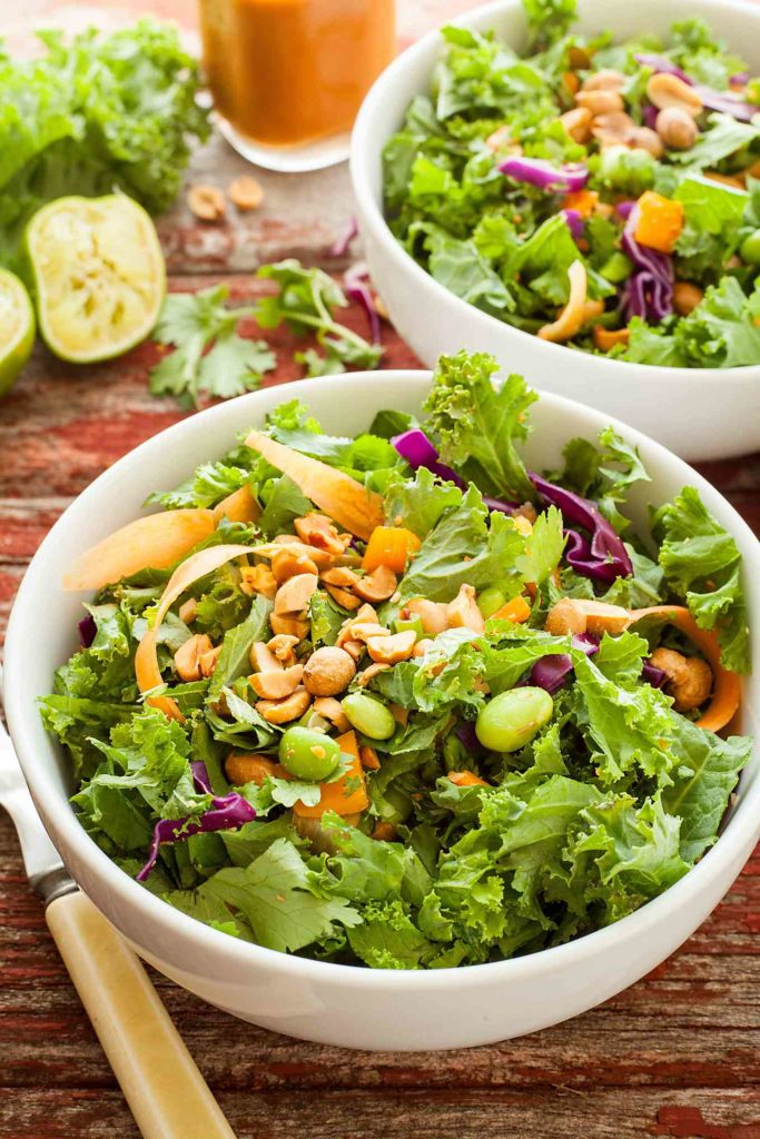 two bowls of healthy green salad with peanut butter dressing
