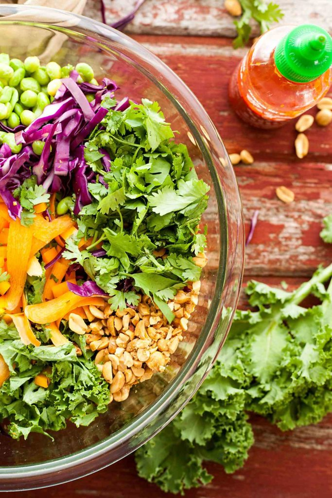 overhead photo of a big bowl of colorful salad and a sriracha bottle