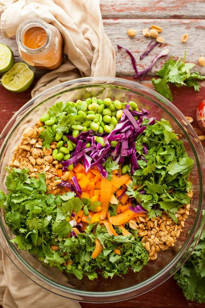 a big bowl of colorful salad with a jar of dressing, limes, and a towel