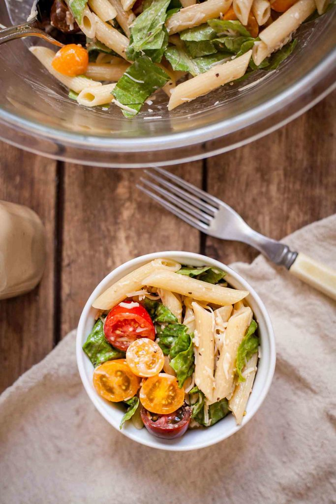 overhead photo of caesar pasta salad on a wood table with a cloth napkin and a fork