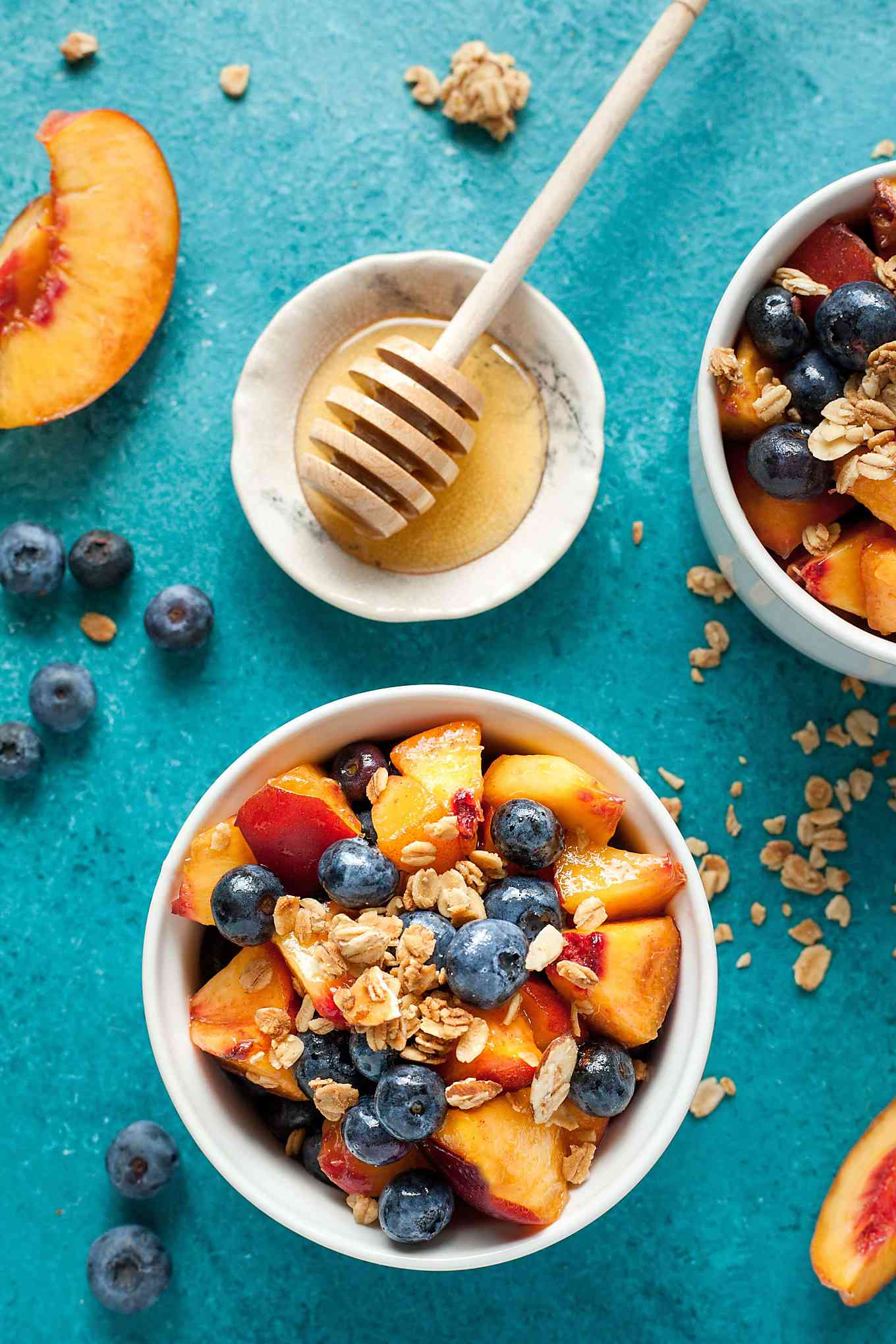 two bowls of summer fruit salad with granola and honey
