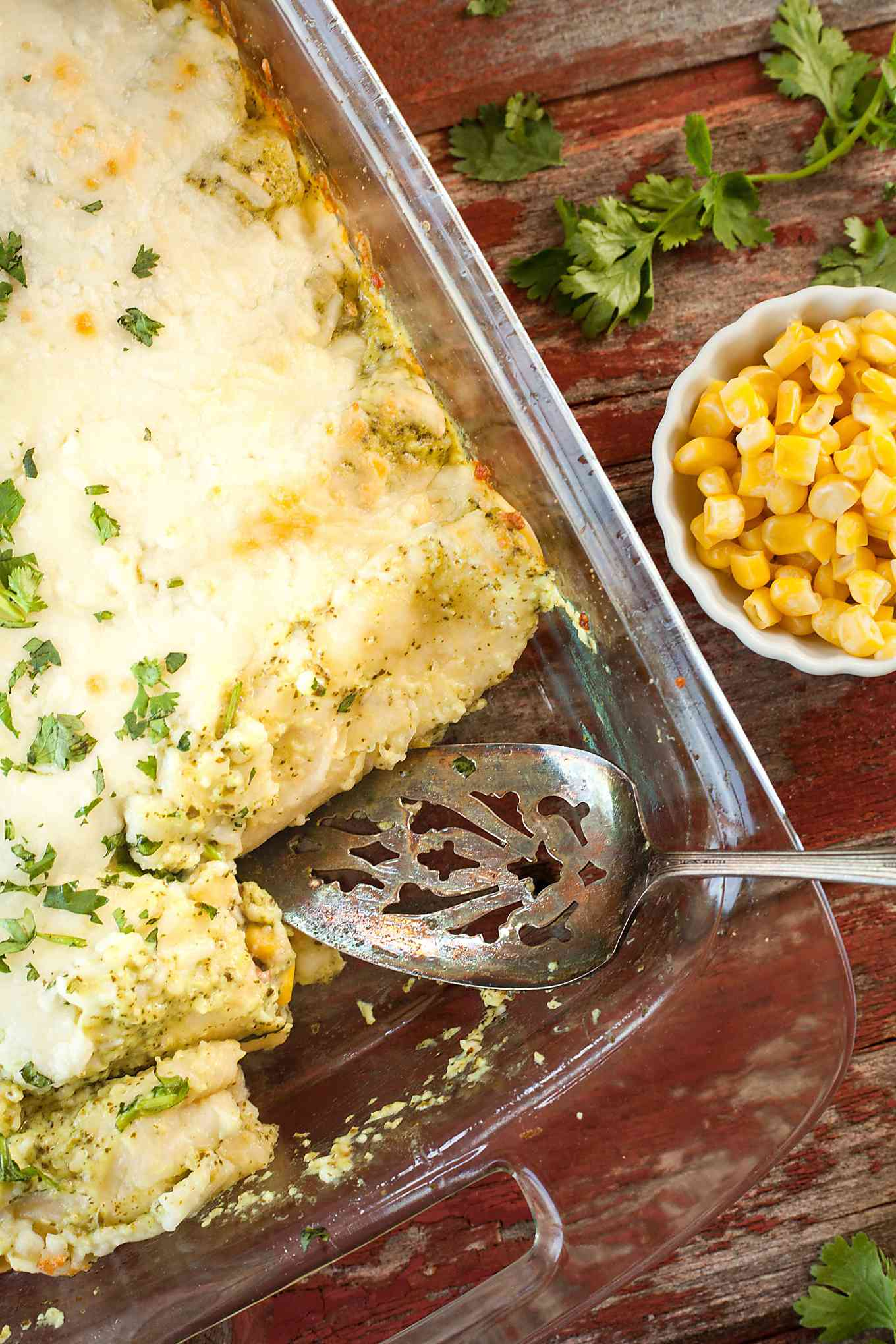 a pan of vegetarian enchiladas with a serving spoon and bowl of corn