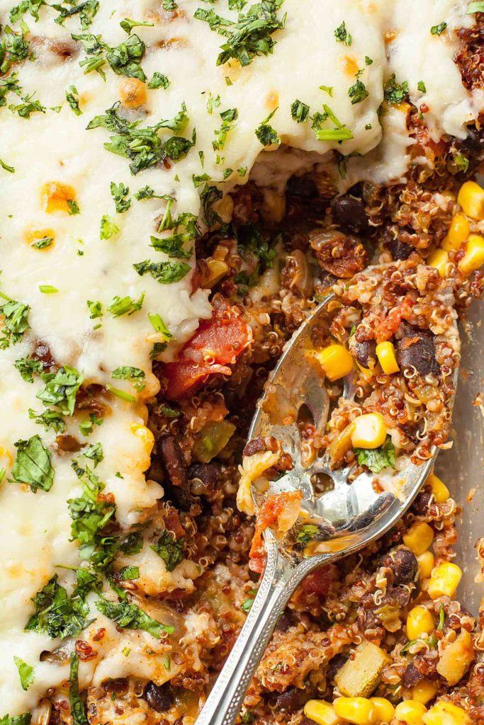 close up photo of crispy quinoa bake with a silver serving spoon