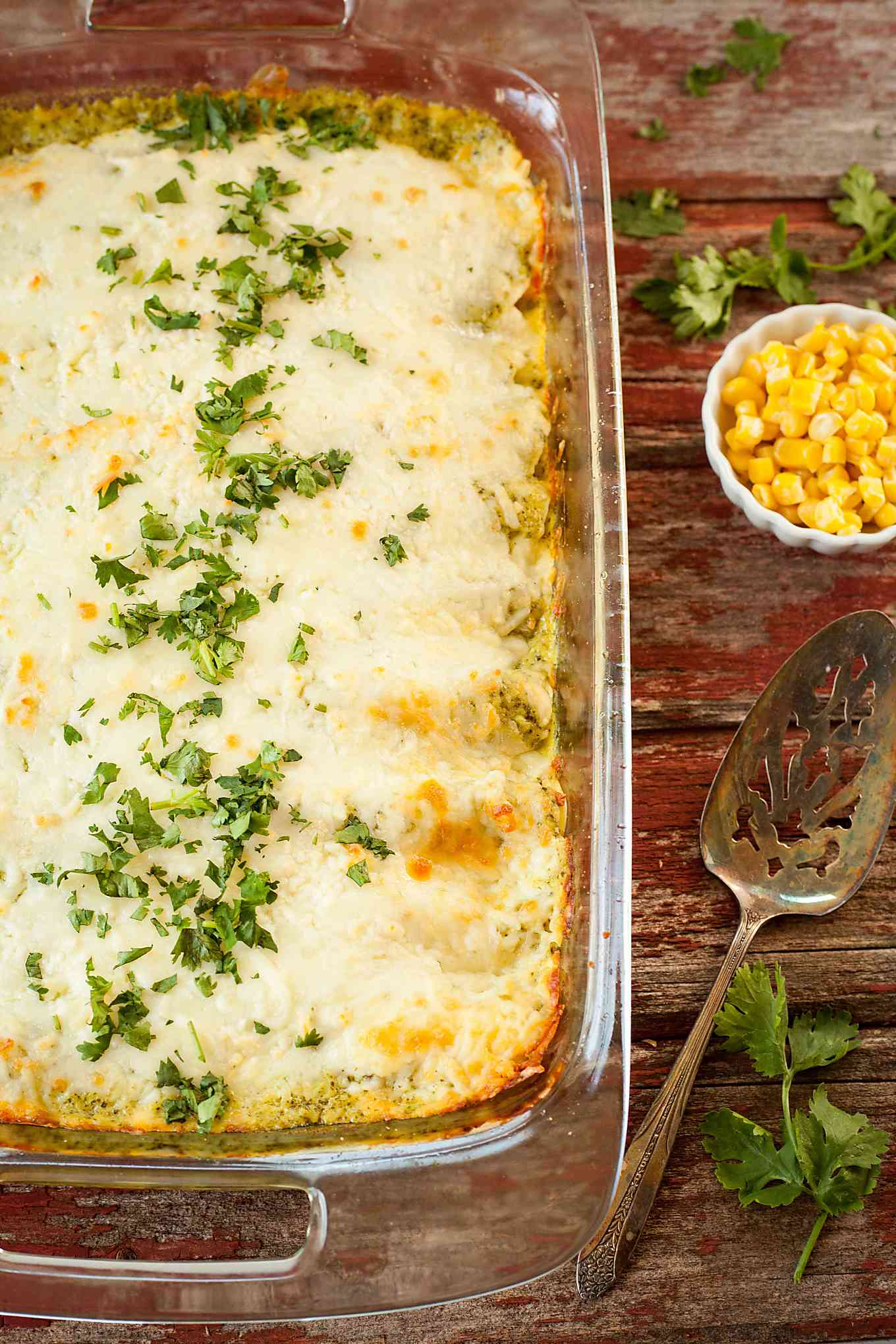 a pan of poblano cream enchiladas with a serving spoon and bowl of corn