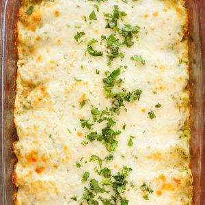 a glass pan of cheesy poblano enchiladas