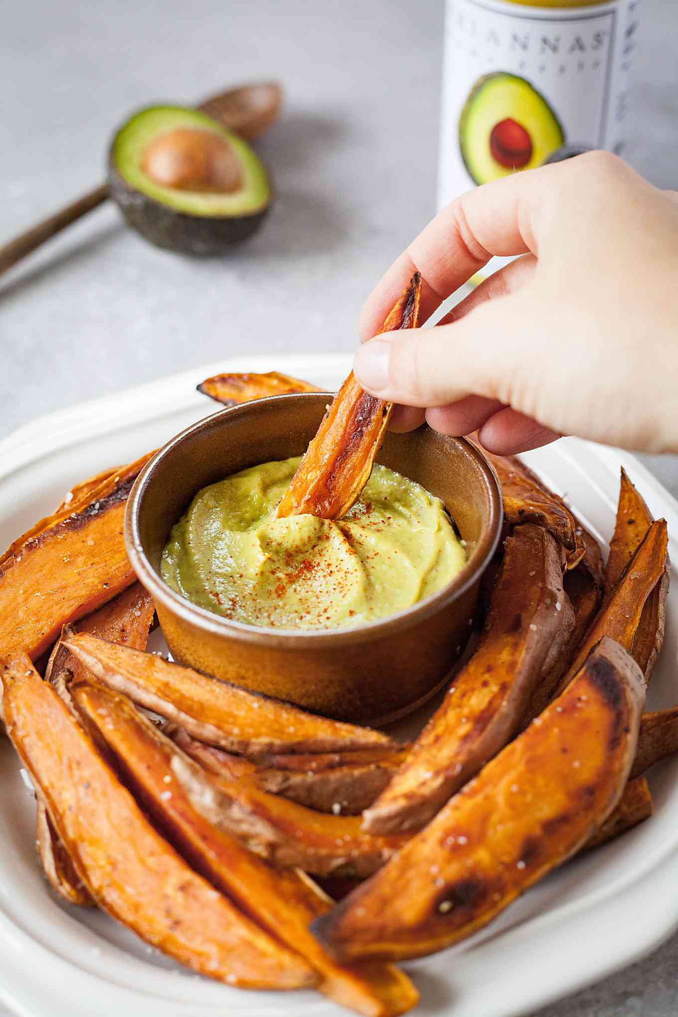 image of hand dipping sweet potato fry in spicy mustard