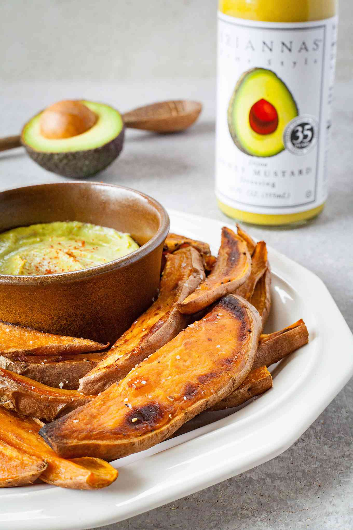close up of side image of sweet potato fries on plate with bowl of spicy mustard and dressing avocado and spoon in background