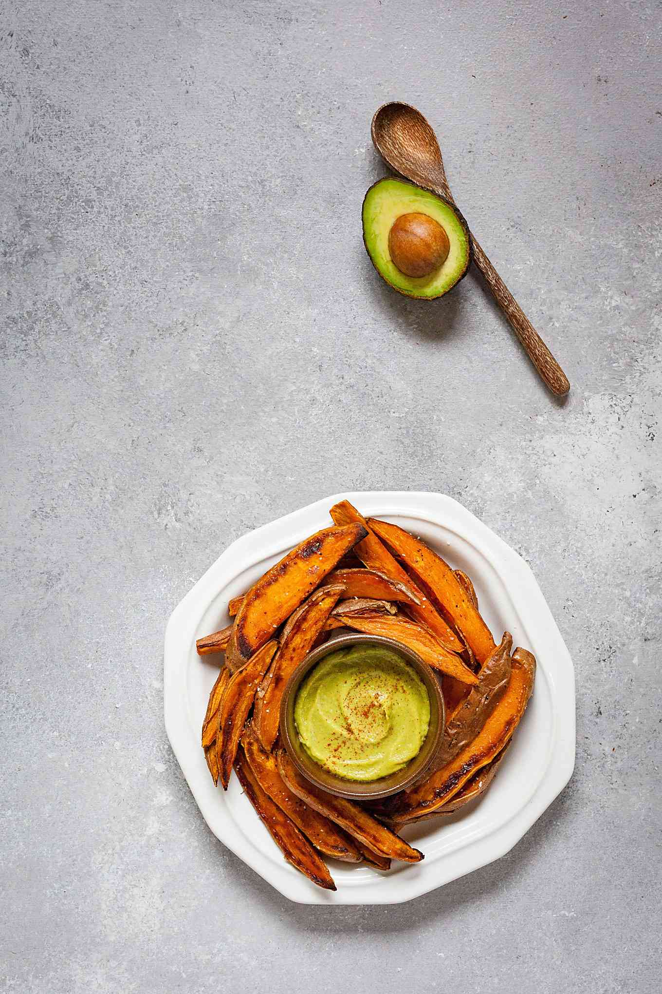 image of wooden spoon and avocado on table with white plate of sweet potato fries and bowl of mustard