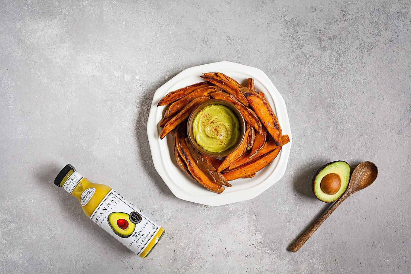 image of plate with sweet potato wedges with a small bowl of spicy honey mustard in middle. Briannas fine salad dressing and wooden spoon next to avocado on table