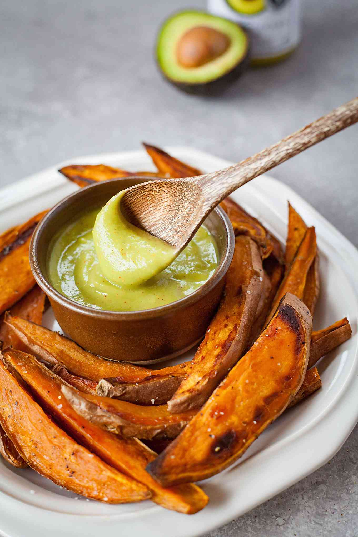 close up image of sweet potato fries on plate with wooden spoon dipped in bowl of mustard