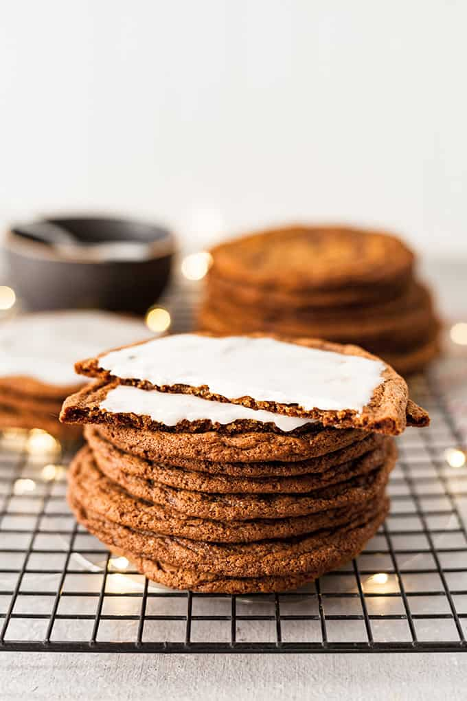 a stack of giant ginger cookies with one covered in icing and cut in half