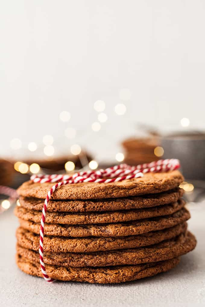 a stack of thin ginger cookies tied with red and white string in front of twinkle lights