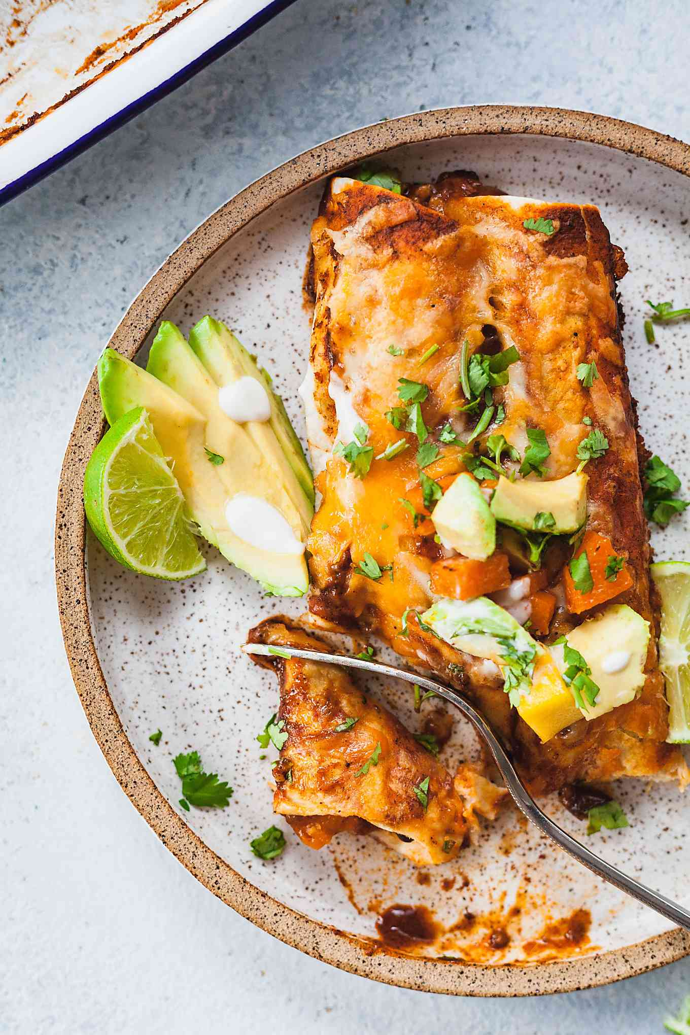 rustic plate with two butternut squash enchiladas being cut into with a fork