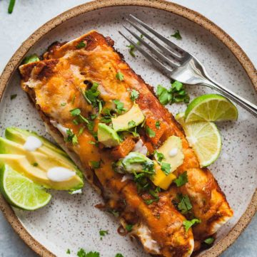 a speckled plate with two butternut squash enchiladas, limes, and avocado