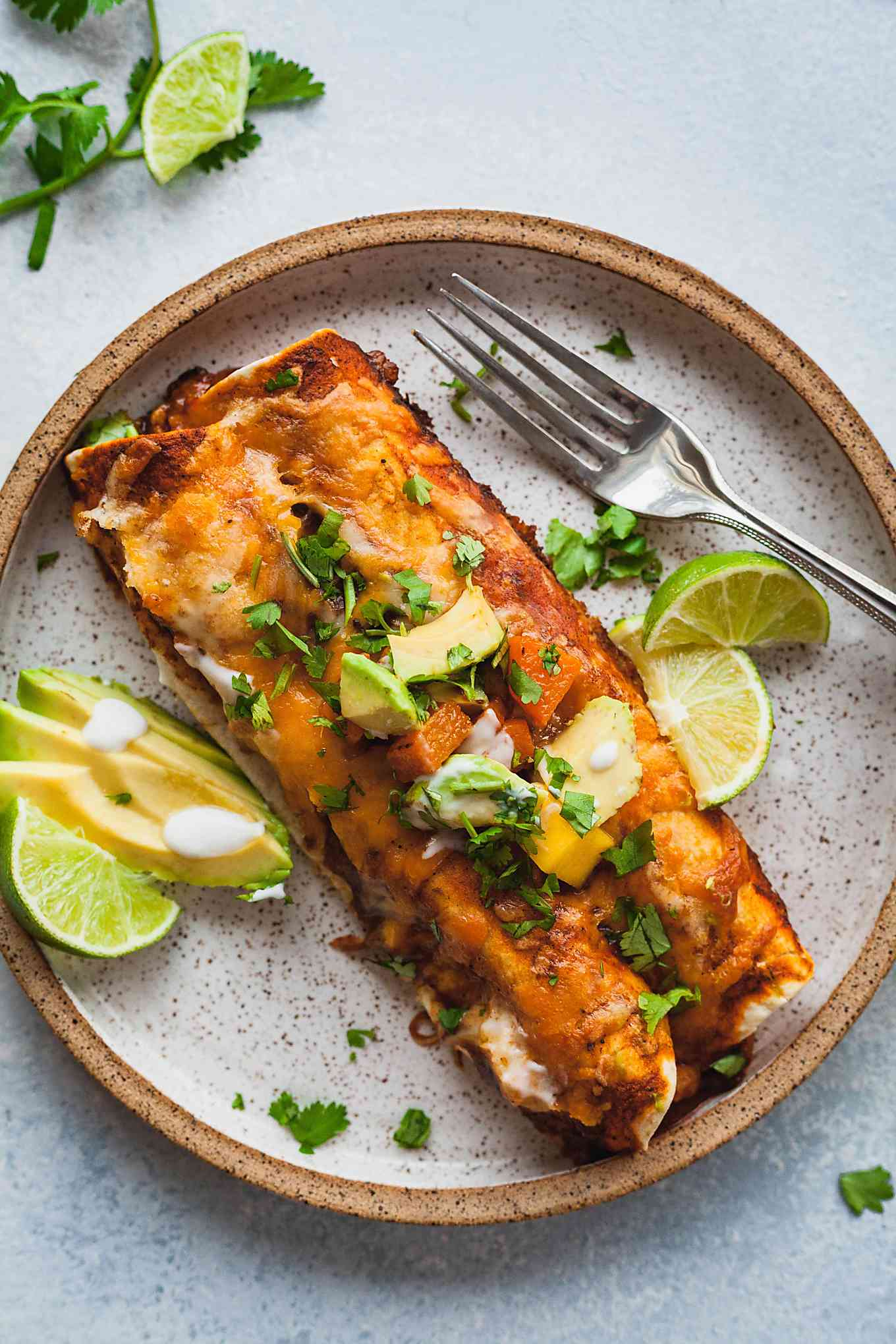 vegetarian enchiladas on a rustic plate with avocado and lime