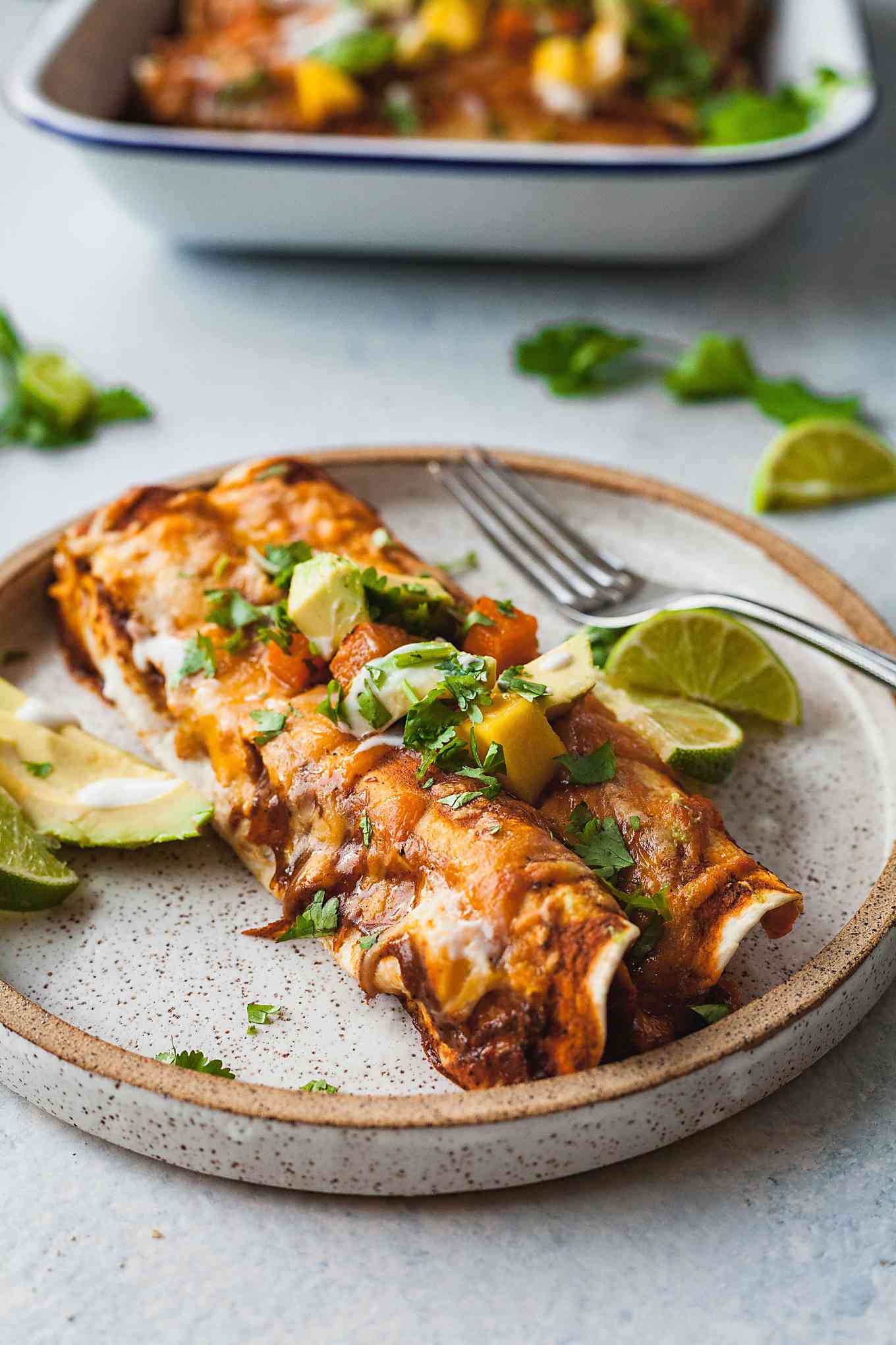 two black bean and butternut squash enchiladas on a rustic plate with avocado, limes, and a fork