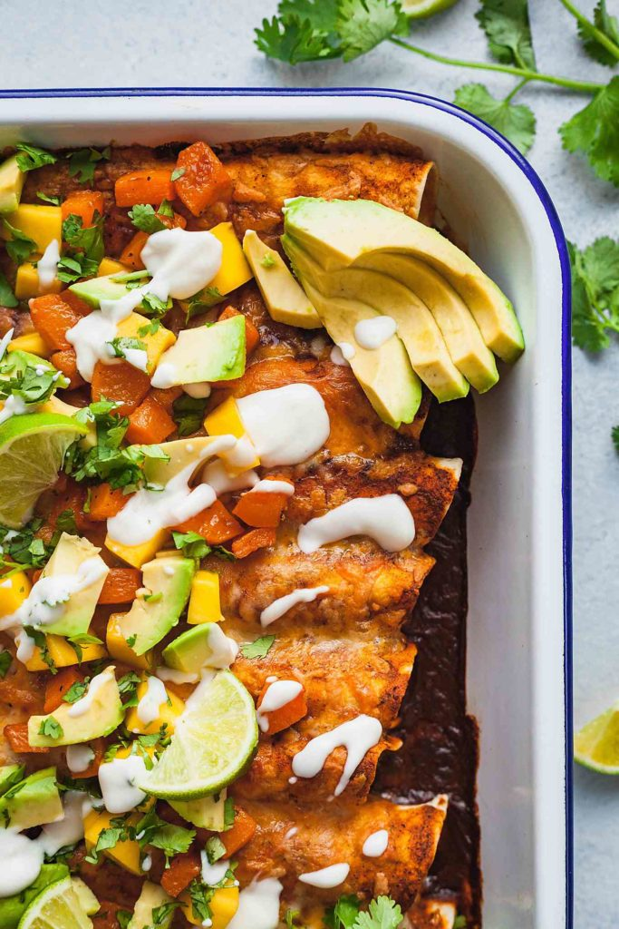 a pan of butternut squash enchiladas topped with avocado, mango, lime, and cilantro