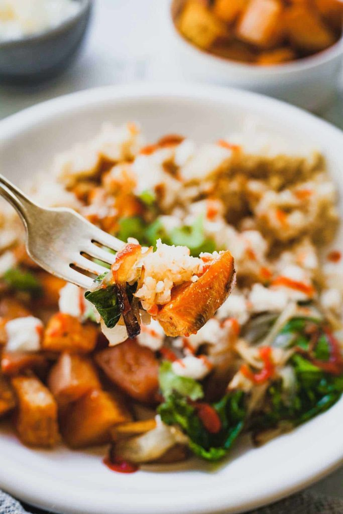 close up of fork with Roasted Sweet Potato Bulgur with bowl in background