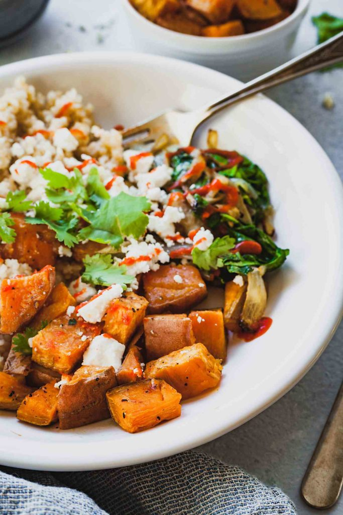 close up of Roasted Sweet Potato Bulgur Bowl with fork in bowl
