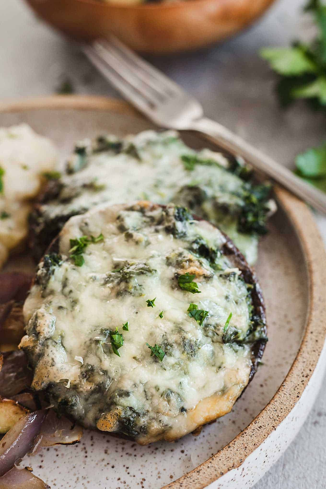 spinach and cheese stuffed portobello mushrooms on a speckled plate