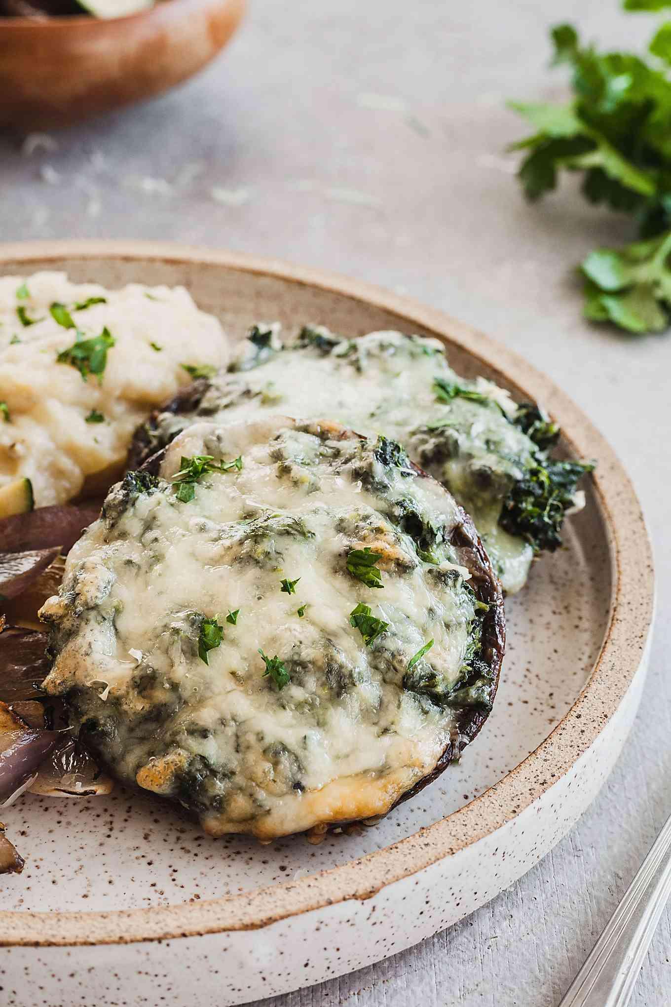 spinach stuffed portobello mushrooms on a speckled plate