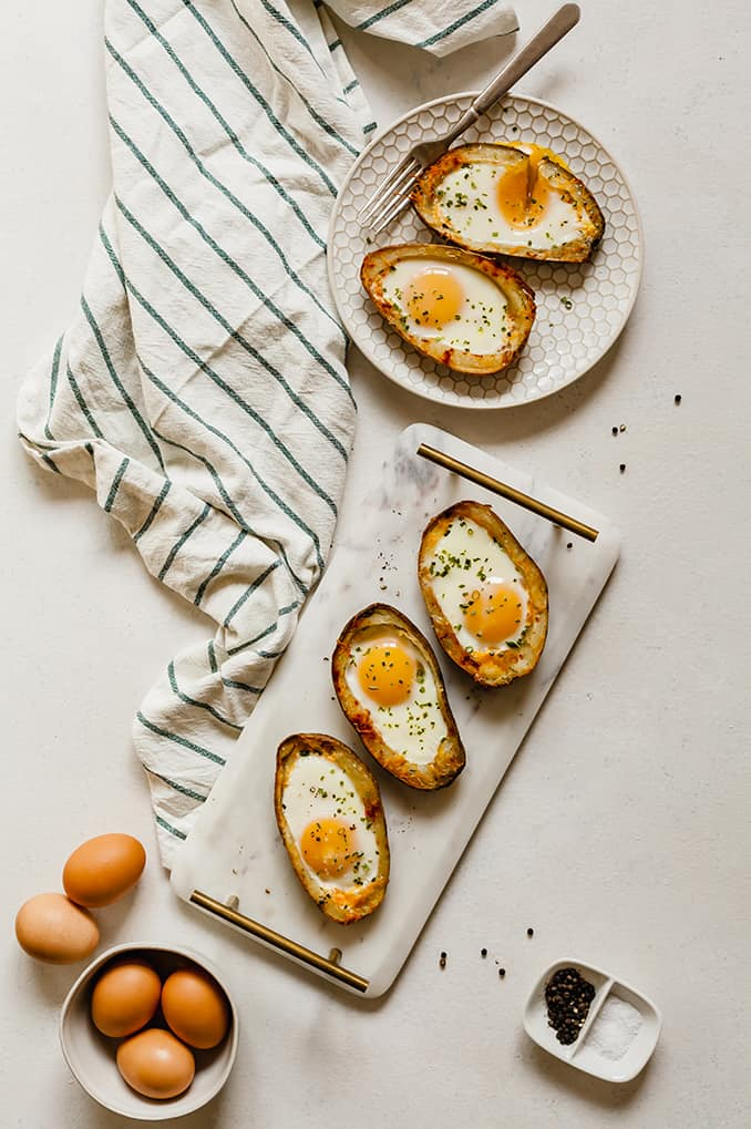 image of plate with two potato boat eggs with three boat eggs on marble tray with bowl of uncooked eggs and spices in trays with striped towel on table