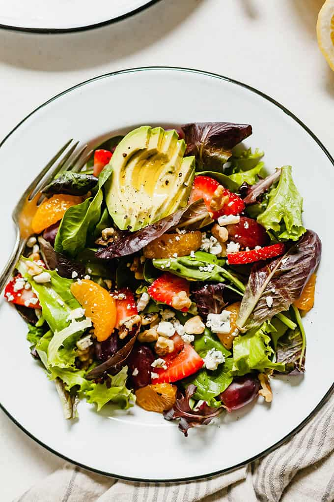 Summer Salad with Fruit - Tangy gorgonzola cheese, crunchy walnuts, juicy mandarin oranges, sliced strawberries, plump grapes, and leafy greens. All dressed in a light oil and lemon juice dressing! #mandarinoranges #strawberries #grapes #walnuts #gorgonzola #spinach #lemon #oliveoil