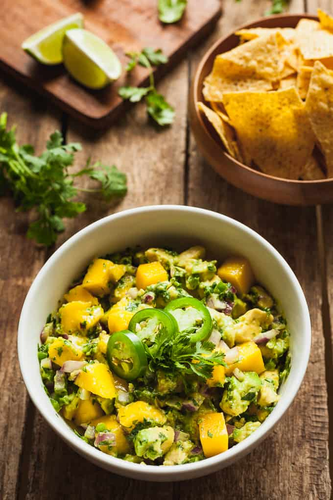 a bowl of mango salsa with avocado, chips, herbs, and lime