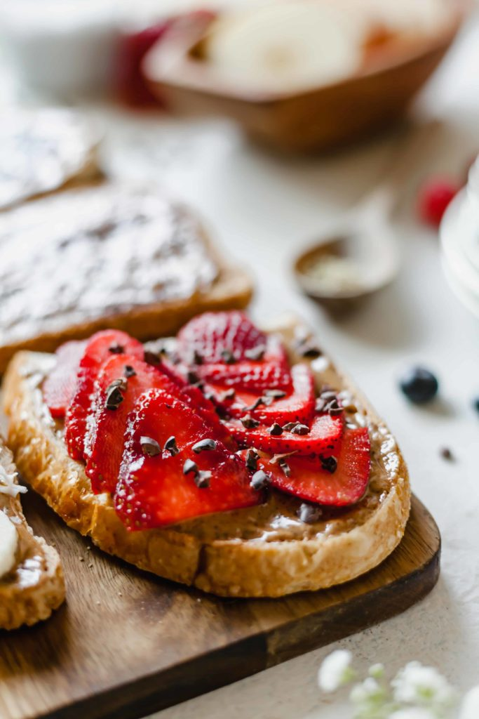 An almond butter toast bar can put together delicious combos like this - toasted sourdough bread, sliced strawberries, and cacao nibs. A healthy, delicious, sweet snack! #sweet #snack #cacao #strawberry #strawberries #sourdoughbread #almondbutter #toast #nutbutter