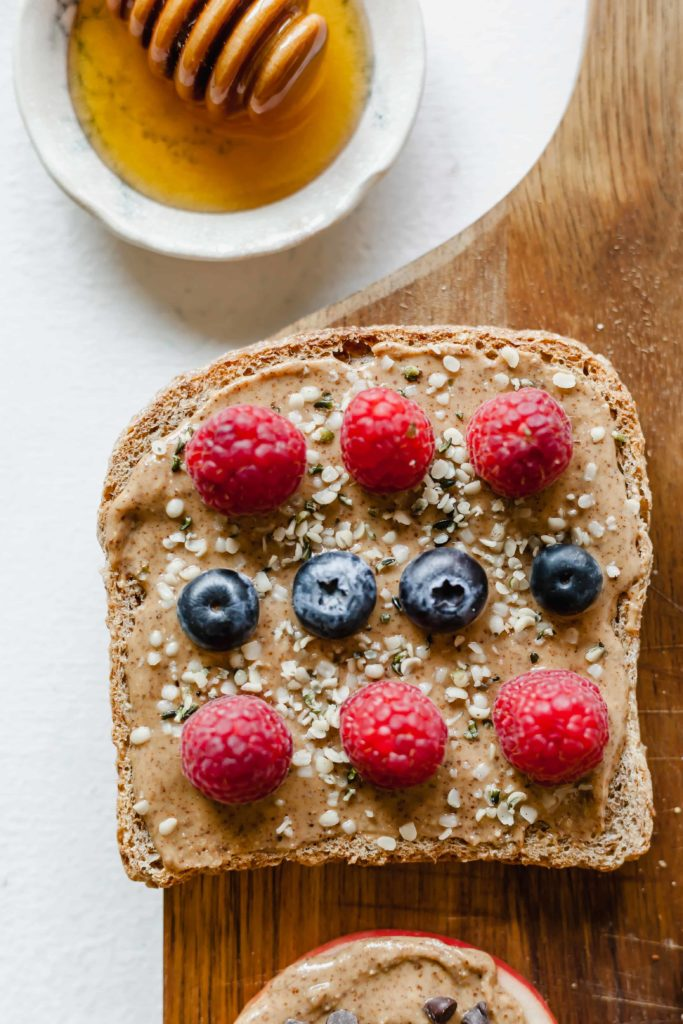 top view image of almond butter toast topped with raspberries, blueberries, hemp hearts with small bowl of honey on top