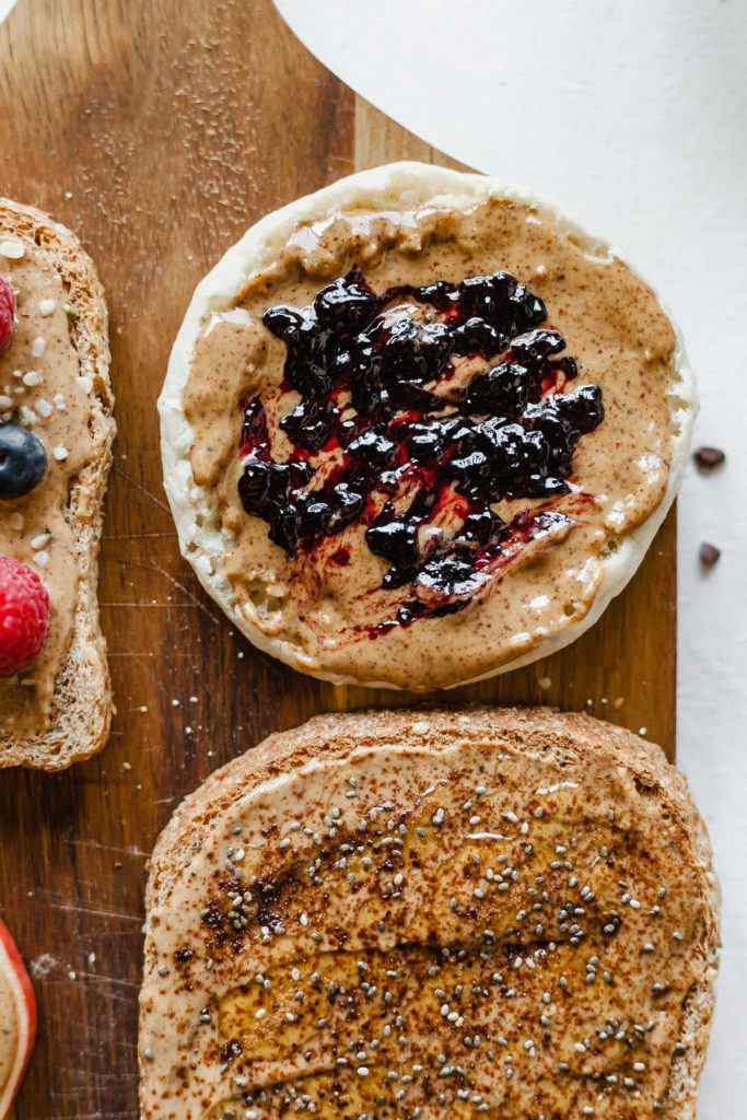top view of almond butter toasts with fruit preserves, honey and chia seeds