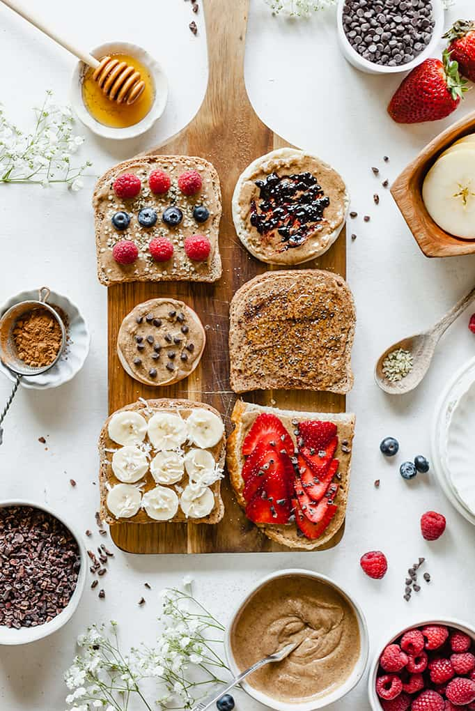 top view image of almond butter toast bar with ingredients on top  wooden board and bowls of ingredients on white table