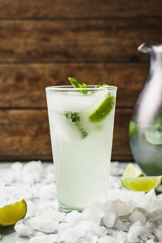 a glass filled with a mojito cocktail surrounded by ice