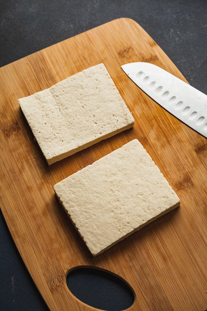 two slabs of tofu on a cutting board with a knife