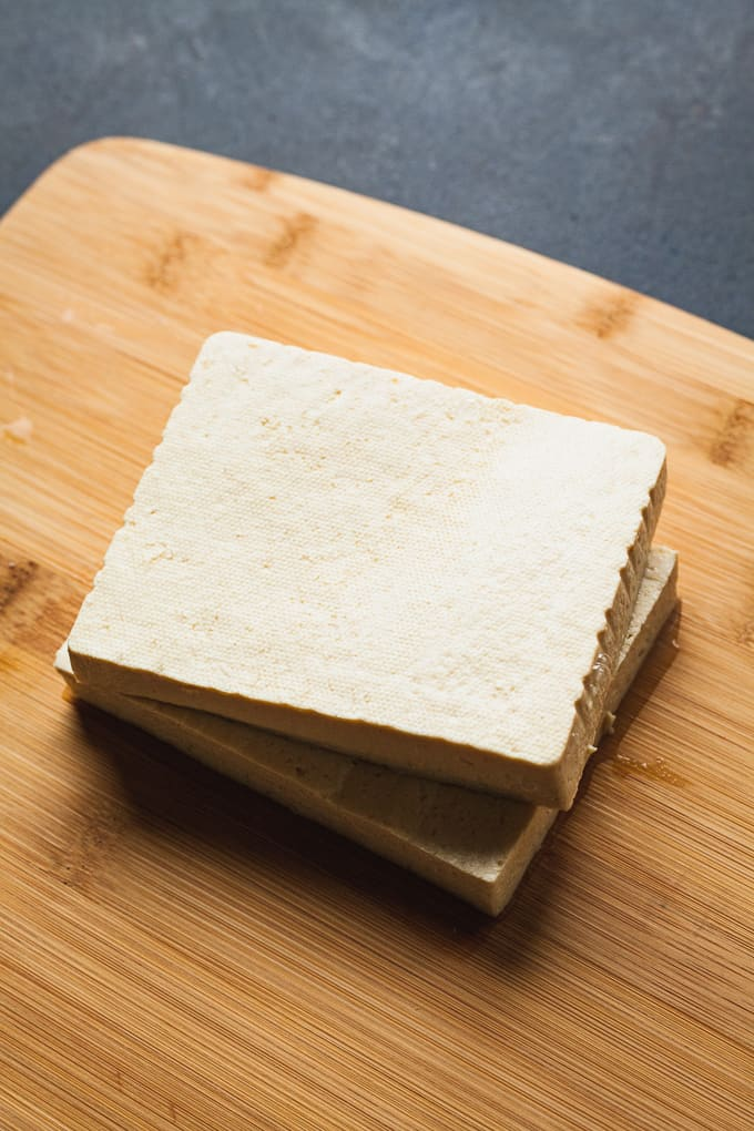 two slabs of tofu on a cutting board