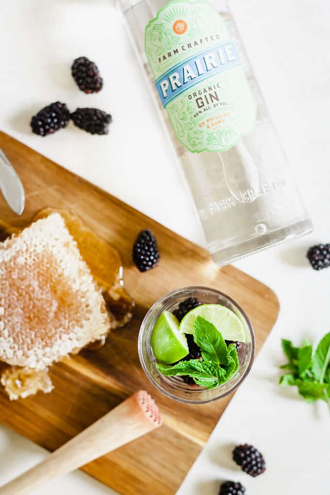 wooden board with raw honey and blackberries. Topview of glass cup with whole ingredients and masher