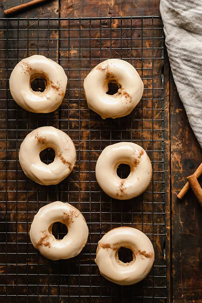 Chai Baked Donuts on a black cooling rack, on top of a wood board with cinnamon sticks and a grey striped linen cloth